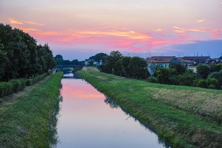 Landscape with the image of chanel in Rovigo, Italy, at sunset
