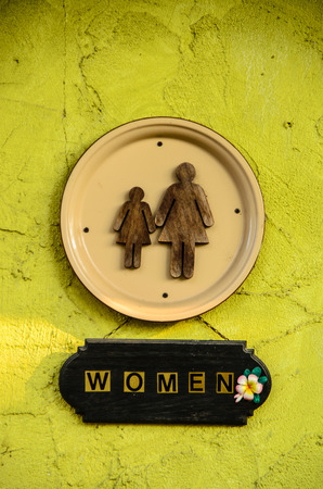 restroom sign: Chic women restroom sign on yellow-green wall