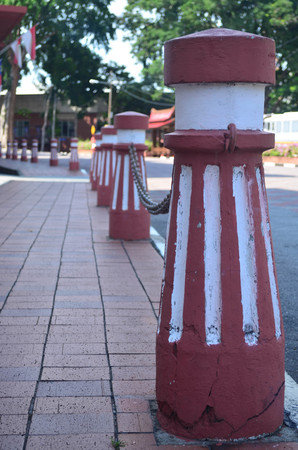 split road: Red and white cement post at the walkway