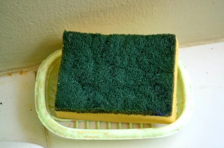 sterilize: Green and yellow sponge on dish soap Stock Photo
