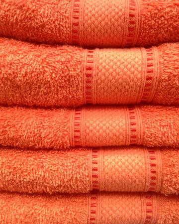 orange washcloth: Stacked of orange towel, close up view