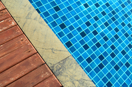 beside: Wooden and marble floor beside blue swimming pool