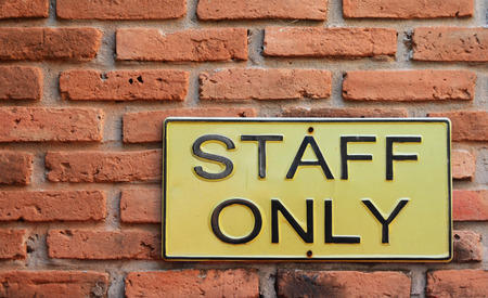 staff only: Staff only sign - yellow metal plate on brick wall Stock Photo