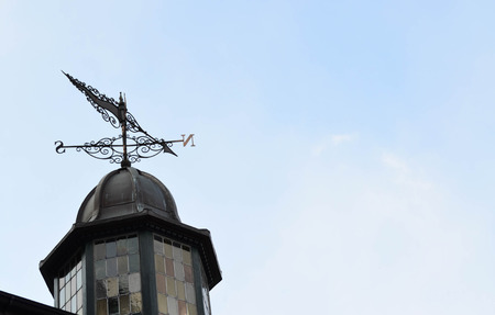 north arrow: Weather vane arrow on rooftop with north and south pointer against cloudy sky Stock Photo