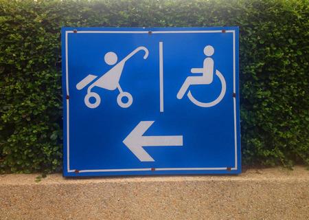 Disable and stroller direction symbol on blue metal sheet Banco de Imagens