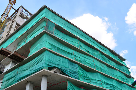 debris: Under construction building wrapped with green net for debris safety Stock Photo