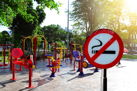 No smoking sign over colorful exercise equipment in public park under sun light - healthy concept Stock fotó