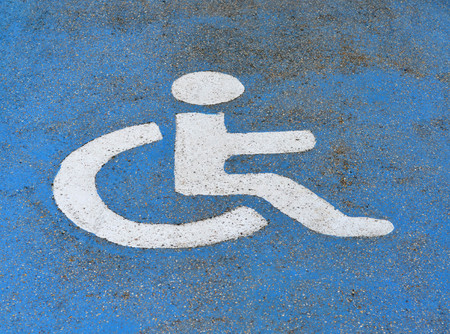 disabled parking sign: Handicapped or disabled parking sign painted on blue asphalt Stock Photo