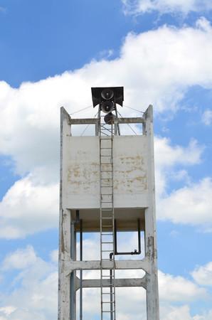 municipal utilities: Square concrete water tower tank against hazy blue sky