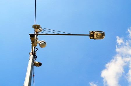 Loudspeaker and CCTV camera on lamp post against blue sky Stock Photo