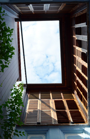 upper floor: Blue airy terrace with brown wooden window on the second floor, bottom view - architecture concept