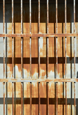 wire mesh: Rusty metal sheet fence with grille under sun light and shady Stock Photo