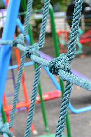 Close up image of weathered knot rope climbing net at children playground, as a symbol of trust, teamwork and collaboration Stock Photo