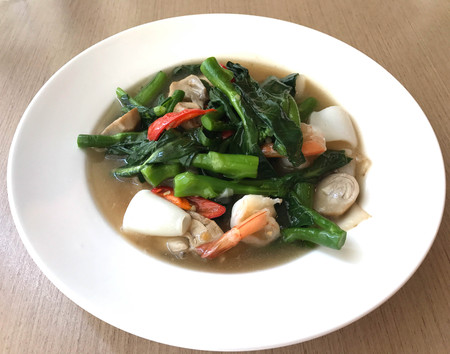 Tasty wide rice noodle in creamy gravy sauce with shrimp and squid, traditional Chinese and Thai style food or called in Thai Rad Na