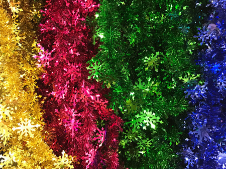 Colorful christmas tinsel and sparkling garland trimming, background and texture