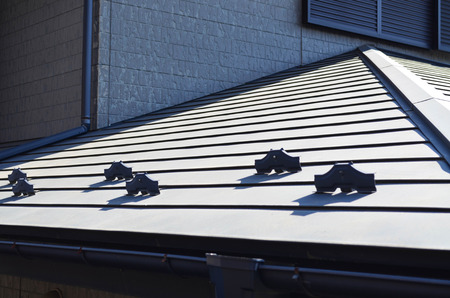 Close up view of rain gutter system and roof protection from snow board (snow guard) on house roof