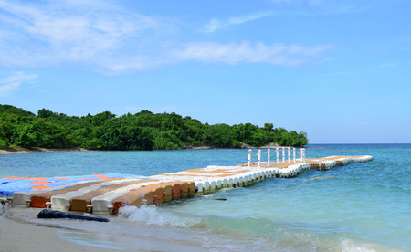 Line of floating pontoon made from plastic on blue sea with green island