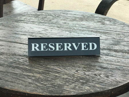 Reserved sign on round wooden table in coffee shop or restaurant