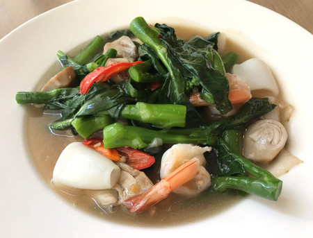 Tasty wide rice noodle in creamy gravy sauce with shrimp and squid, traditional Chinese and Thai style food or called in Thai