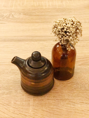 Brown ceramic shoyu jar or japanese sauce and flower on wooden table