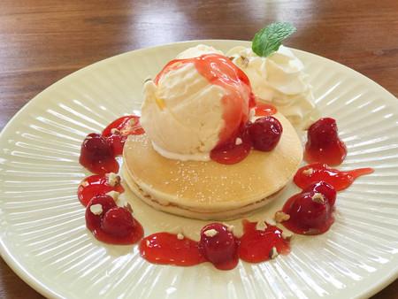 Pancake topped with vanilla ice cream and cherry sauce