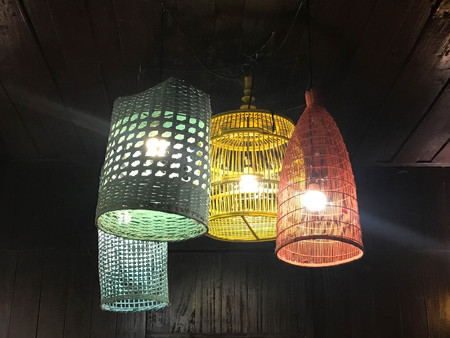 Decorating ceiling hanging lantern lamps in painted wooden and bamboo wickerin different color against black background