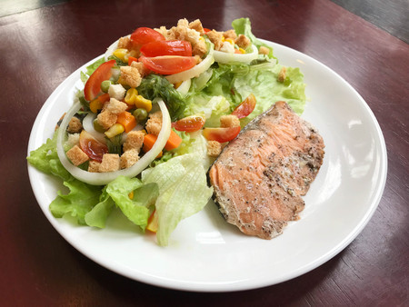 Grilled salmon steak with salad on white plate, side view
