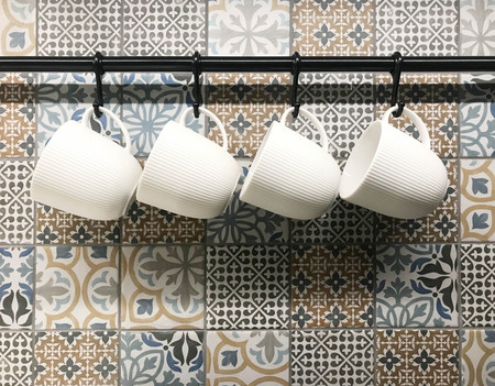 White ceramic cups hanging on hook in front of art pattern tile wall, in coffee shop or kitchenware store