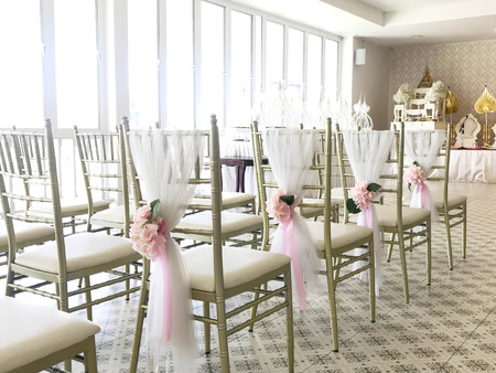 Row of white chairs decorated with bouqet in wedding ceremony, side view