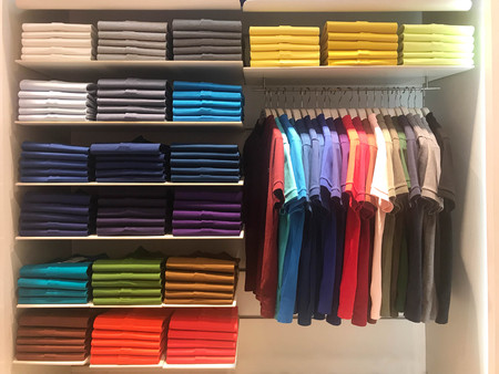 Multi color polo shirts on hanger and shelves for sale in store 스톡 콘텐츠