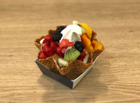 Soft ice cream with mix fruit and wafer on wooden table - selective focus