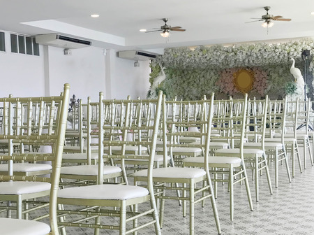 Row of white chairs in wedding ceremony, side view