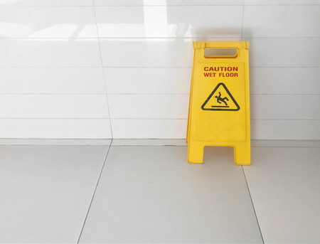 Caution yellow sign stated caution wet floor during janitor cleanup service on ceramic tile floor Stock fotó