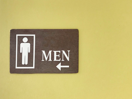 Man or men wooden restroom sign on yellow green cement wall