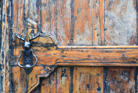 Grunge brown wooden door with reindeer metal door knocker