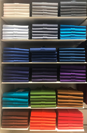 Multi color polo shirts on shelves for sale in store