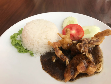 Stir fried soft shell crab with black pepper sauce served with jasmine rice on white plate Stock fotó