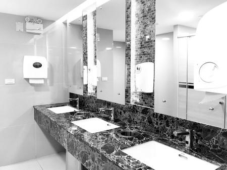Diseño interior de lavabo público y grifo automático en hotel o restaurante moderno o tienda departamental, tono blanco y negro Foto de archivo