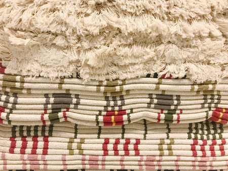 Stack of stripe carpets with tassel