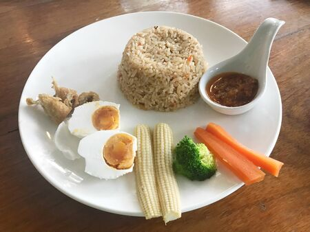 Fried rice with chili paste served with mix vegetable, fried fish and salted egg, Thai food