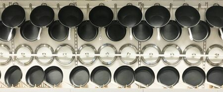 Hanging teflon pans and lids on wall, in kitchenware store 版權商用圖片
