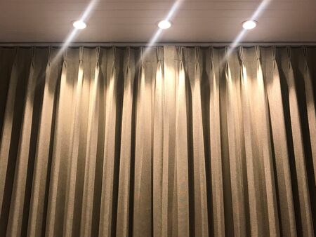 Ceiling with spot lights and top part of curtain in golden brown, interior and architecture concept