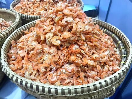 Pile of fresh organic dried shrimp in woven basket in marketplace Stok Fotoğraf
