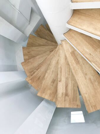 Wood spiral staircase with white wall, interior and architecture concept