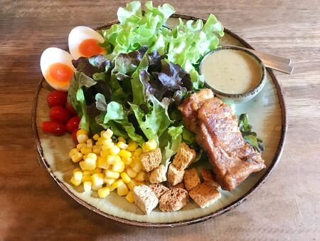 Tasty grilled rib served with organic salad (tomato, lettuce, corn, crispy bread, boiled egg) Stok Fotoğraf