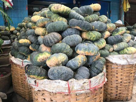 Pile of green pumpkin on woven basket in food market