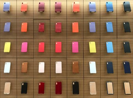 Colorful smartphone case or cover displayed on wooden shelf in phone shop