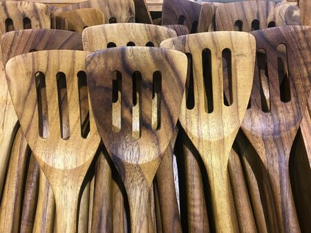 Pile of brown wooden turner or spatula in kitchenware shop