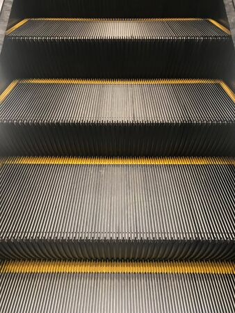 Moving up of electric escalator in shopping mall or department store, close up view