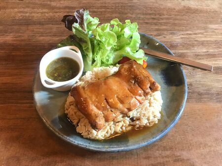 Tasty roasted chicken topped with gravy sauce served with rice, spicy sauce and fresh lettuce and tomato